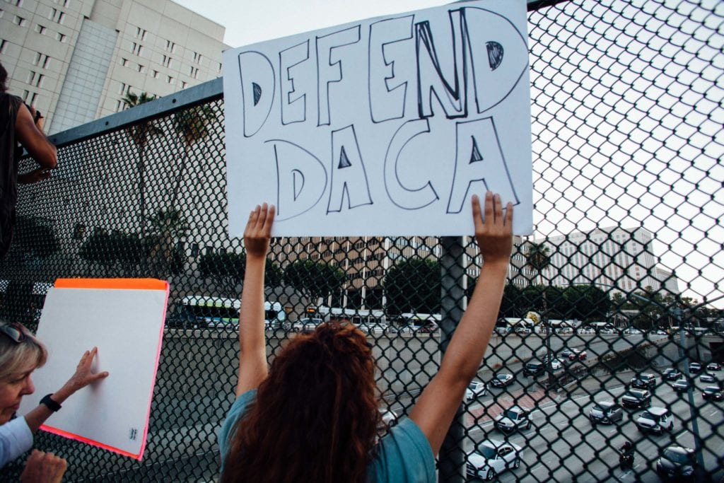 "A protestor holds up a ""Defend DACA"" sign to drivers above the 101 Fwy in downtown Los Angeles."