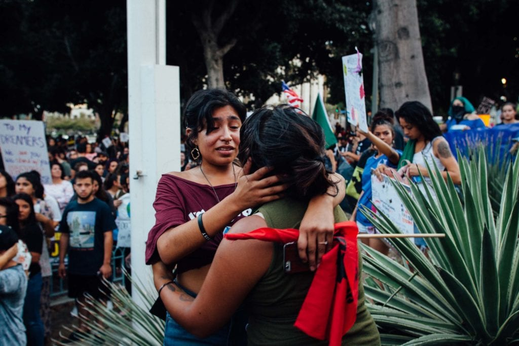 Sisters support each other in their upset at Trump's decision to rescind DACA at the City Hall rally in Los Angeles, CA.