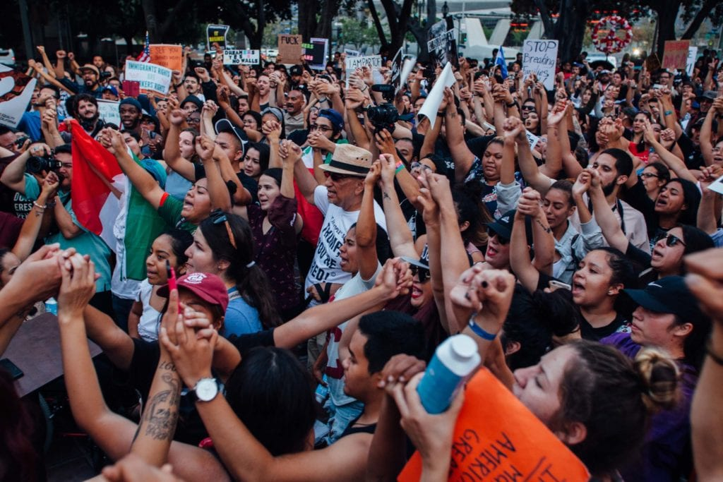 Protestors hold hands and pledge to support and fight for each other at the end of the rally at City Hall in downtown Los Angeles.