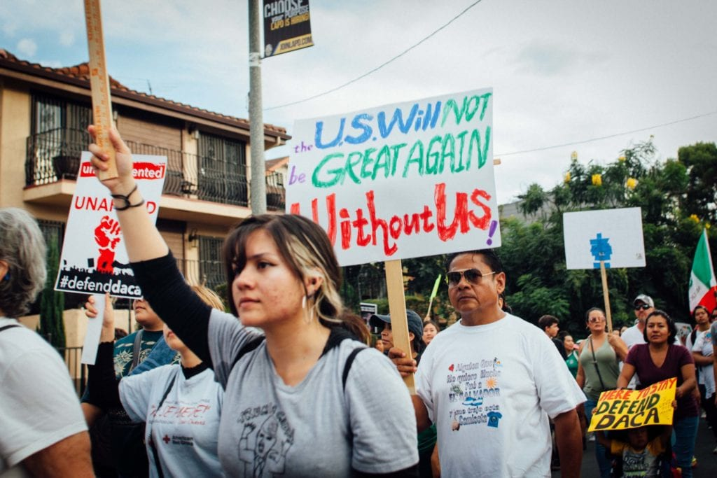 A protestor marching in Echo Park towards Olivera Street in downtown Los Angeles.
