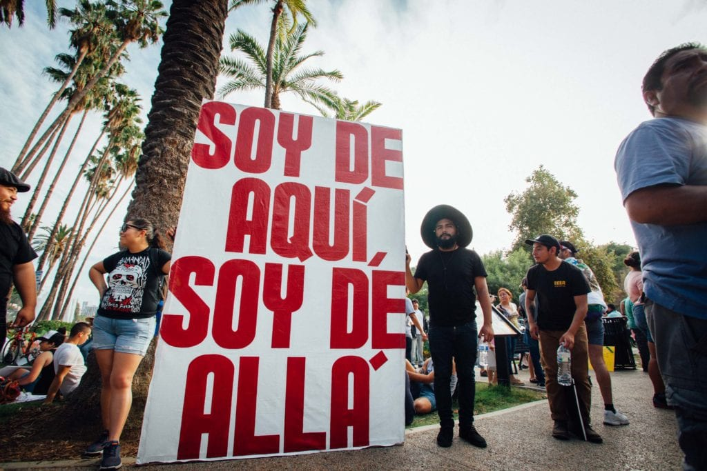 "Artist Emmanuel Galvez (right), age 26, grew up in Mexico City and Los Angeles and is a DACA recipient. He created this illustration to send a message to Trump. The other side of his sign says, "" Soy de Aqui, Soy de Alla."" He wanted to convey the message that we all belong here, and we all belong there. His friend Alex Gonzalez (left) took the day off of work to attend the march."