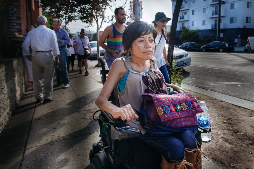 Though the sidewalks were lined with uneven cracks, Rosalba Rios trekked onward in her wheelchair to join the march up Alvarado St. She works as a mental health therapist in Inglewood, CA.