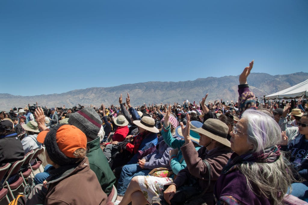 First-timers to the Manzanar Pilgrimage raise their hands. Many new people were inspired to attend this year due to similarities between the Trump administration's rhetoric and policies against immigrants and Muslims, and the fate of Japanese-Americans during WWII. Photo by Joanne Kim