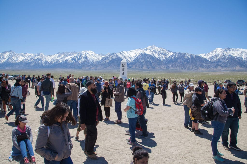 "Attendees of the Manzanar Pilgrimage in the camp's cemetery. In the middle stands ""I Rei To/Soul Consoling Tower,"" a monument by Ryozo Kado installed in August 1943 to honor those who are buried there. Families collectively paid for its construction. Photo by Joanne Kim"