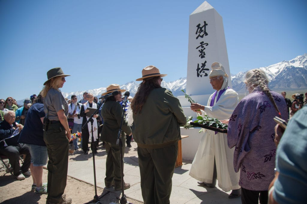 During the Shinto ceremony, National Park Rangers are given leaves to place on the I Rei To monument to honor those who were interned at Manzanar. Rangers worked with the Japanese-American community in creating the Manzanar Historic Site's Museum and the re-creation of the barracks and buildings. Photo by Joanne Kim