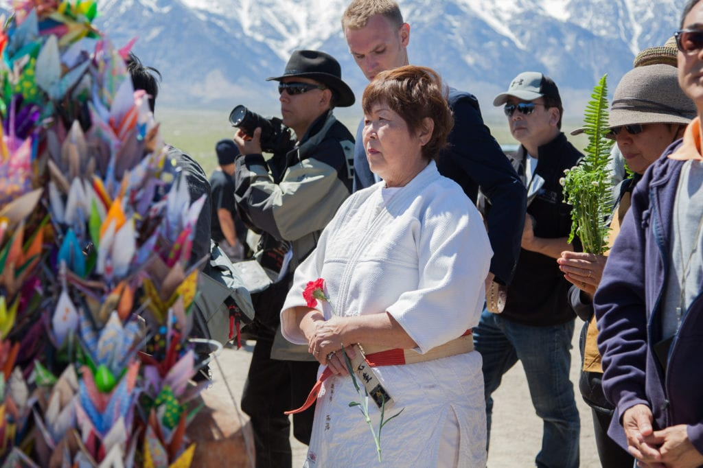 An attendee holds a flower during the interfaith service to place on the I Rei To tower to honor those who were interned at Manzanar. Photo by Joanne Kim
