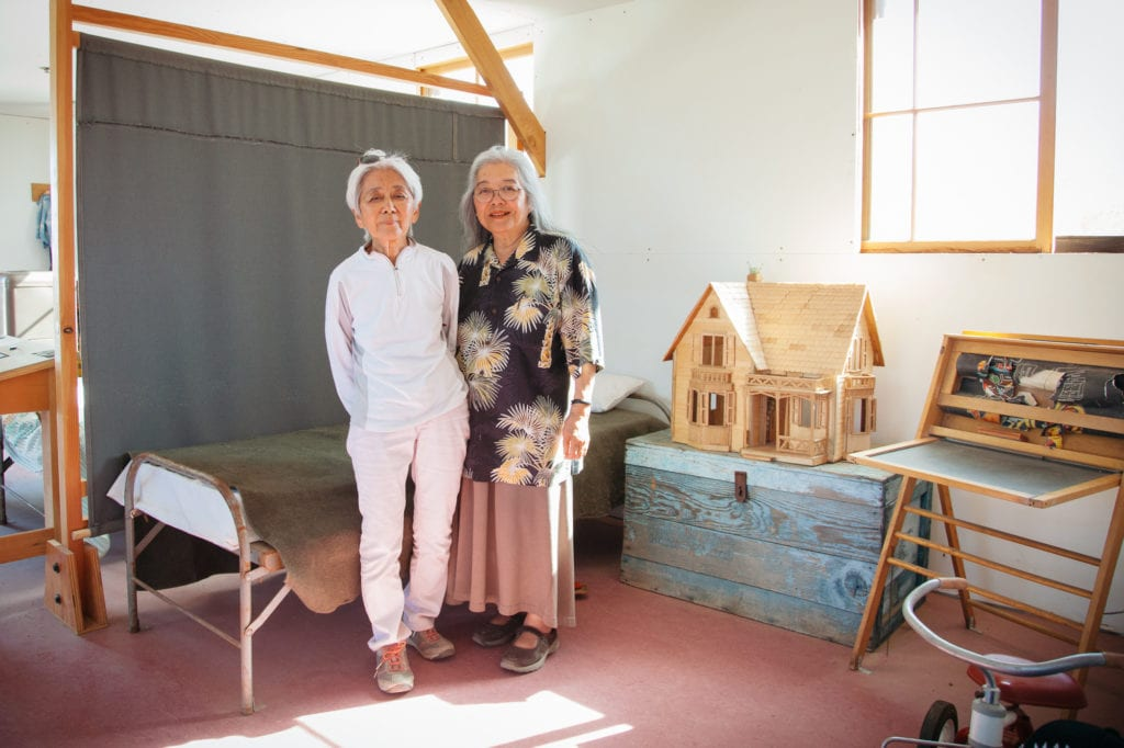 Former Manzanar child internees Irene Hadeishi, left, and her sister Marge Taniwaki, right, in a re-created children's room. In order to make the re-creations of living spaces accessible, National Parks was required to make the living quarters much nicer than what was the reality for Irene and Marge and other families. They slept in cots separated only by sheets from other families with floors made of wood beams with space between them so the dust would come up constantly from the ground into their eyes and mouths. Photo by Joanne Kim