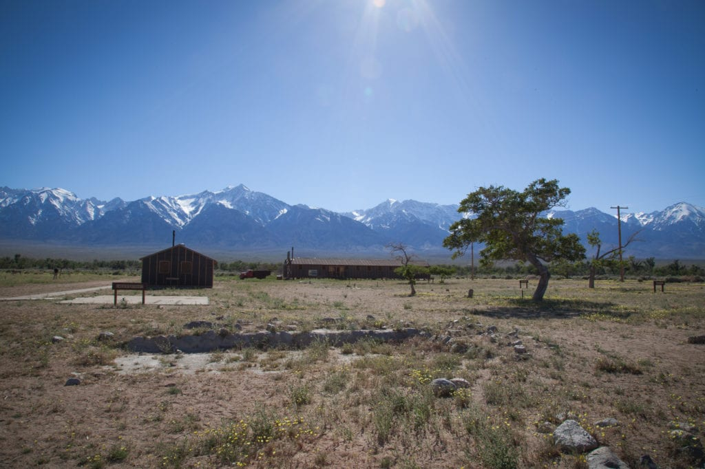 Recreation of the latrine and dining hall at the Manzanar concentration camp located in a valley below the Eastern Sierras (background). Photo by Joanne Kim