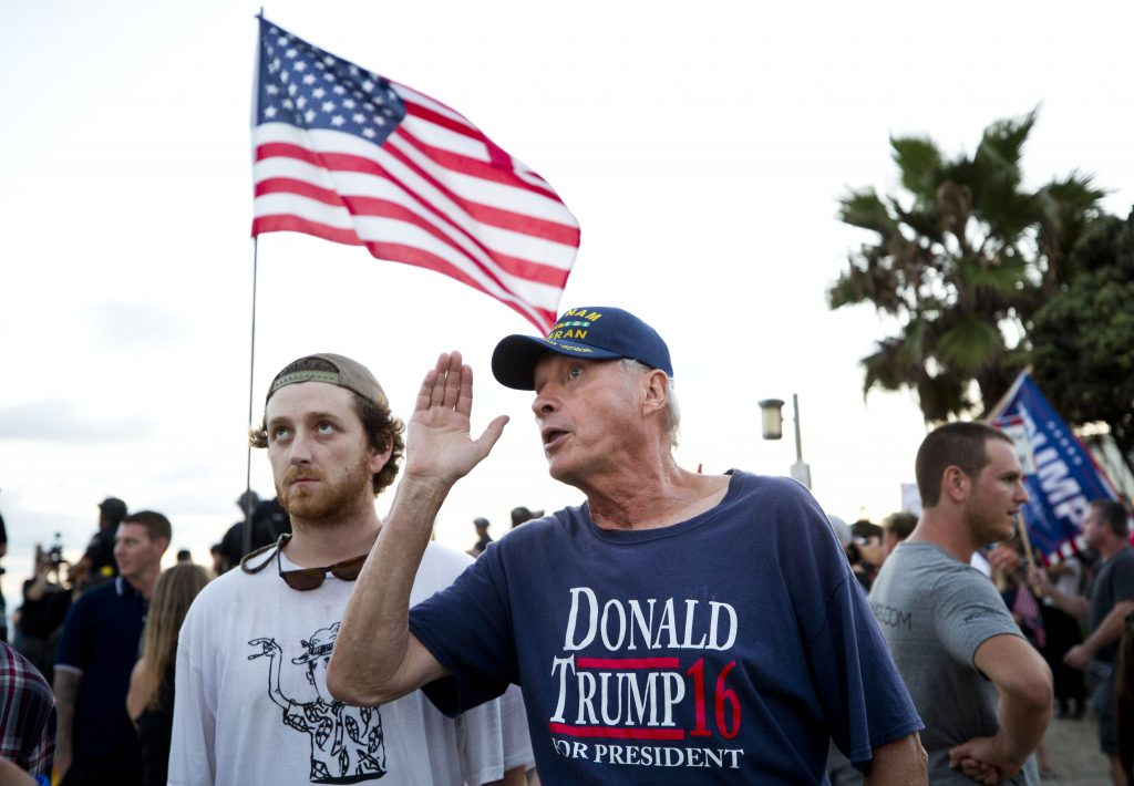 Martin (no last name given), a Vietnam veteran and Trump supporter, talks to younger pro-Trump and anti-immigration protesters at the Laguna Beach boardwalk.
