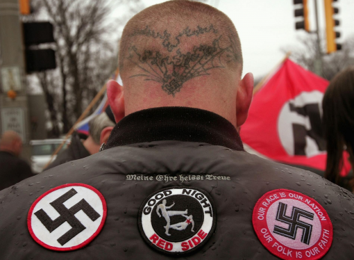 Man with swastika tattoo charged with hate crime after punching man and yelling racial slur
