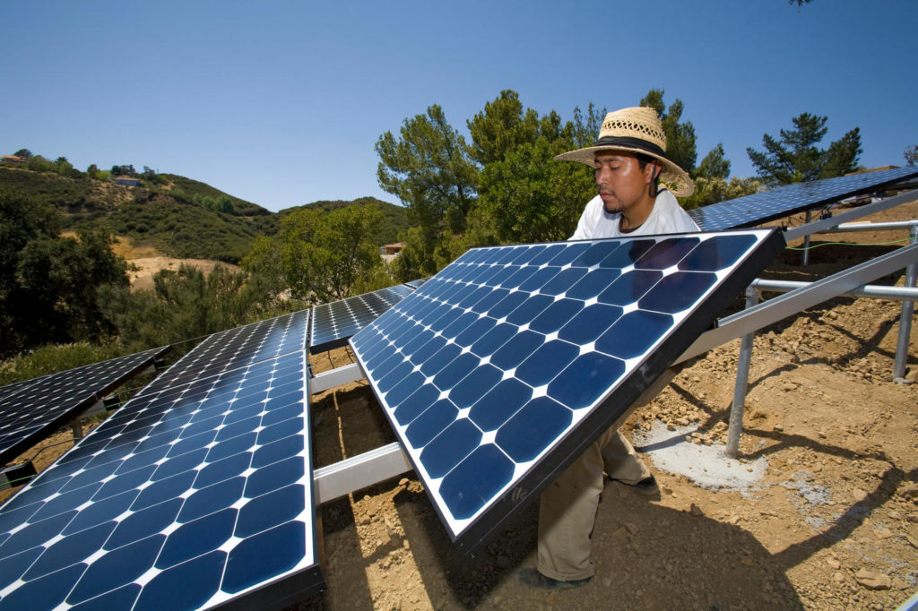 Green workers install a residential grid-tied solar array on a hillside in Malibu, Installation by Martifer Solar USA, CA, USA.