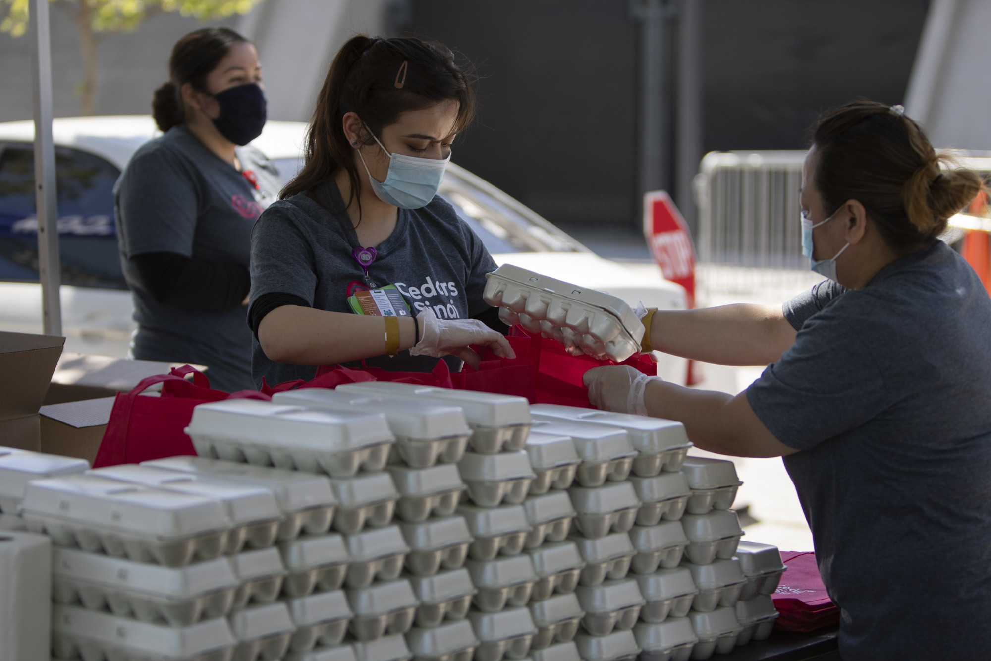 Representatives from Cedars-Sinai prepare bags with a dozen eggs. Each family also receives a week's worth of seasonal fruits and vegetables, 10 pounds of oranges, and information about local public nutrition benefit and incentive programs.