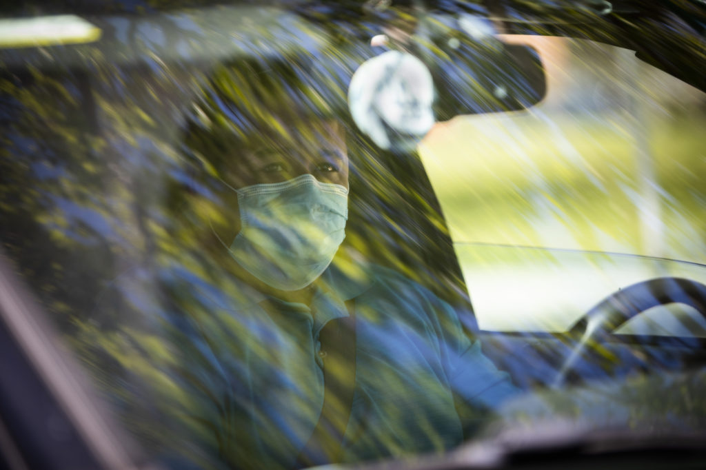 A man in a face mask waits in his car as his trunk is packed with produce and eggs at the Farm Box Program.
