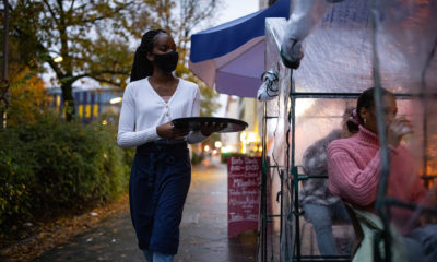 Young waitress serving drinks to customers in outdoor plastic tent wearing a mask. Waiter wearing protective face mask serving drinks at street cafe during pandemic.