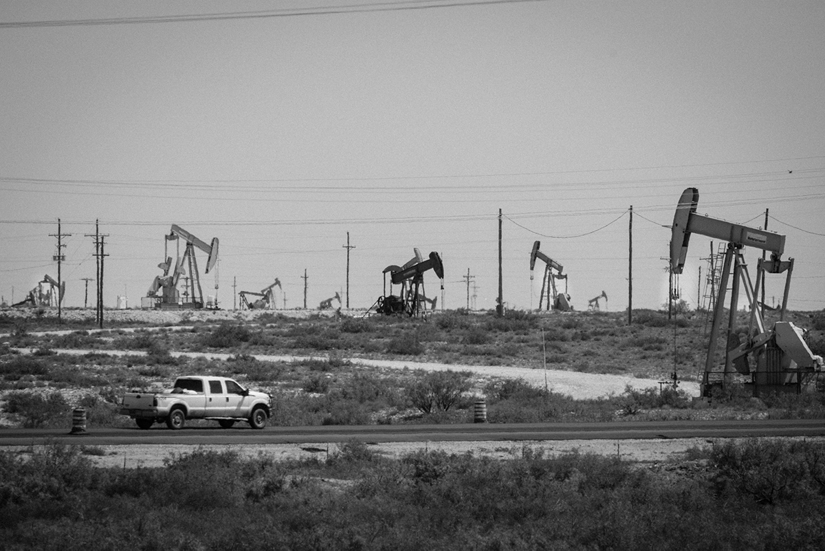 A truck drives in front of a few of the thousands of wells pulling up oil in the Loco Hills area of the Permian Basin north of Carlsbad, NM. Photo by Jerry Redfern.