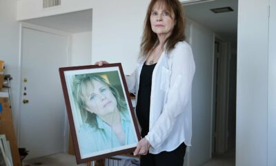 Janice Lynde holds stands in her apartment holding a broken framed photo.